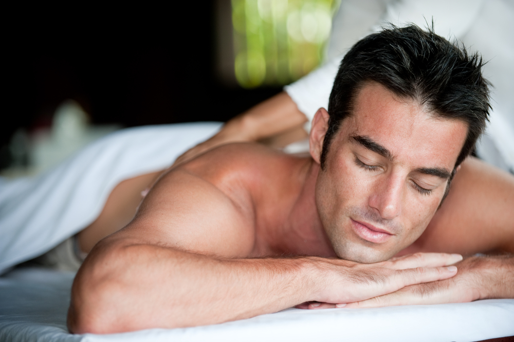 A good-looking man getting a back massage lying down - Leo man's erogenous zones