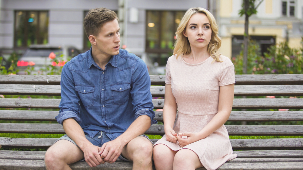 Man and woman breaking up on bench in park - Is the Leo Man Jealous or Possessive