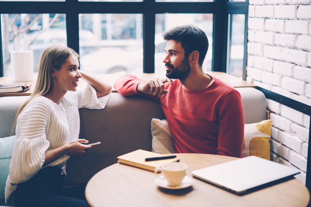 Young woman and man talking during first date in cozy coffee shop - How to Get a Leo Man to Marry You