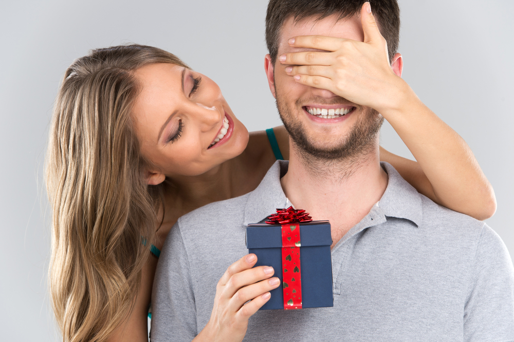 girl standing behind man with gift - Gifts for the Leo Man